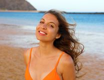Happy woman on the beach. Portrait of beautiful girl with wind fluttering hair. Summer portrait on the beach at sunset. Young. Pretty smiling woman outdoors royalty free stock photos