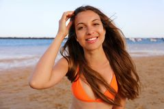 Happy woman on the beach. Portrait of beautiful girl with wind fluttering hair. Summer portrait on the beach at sunset. Young. Pretty girl smiling woman stock photography