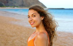 Happy woman on the beach. Portrait of beautiful girl with wind fluttering hair. Summer portrait on the beach at sunset. Young. Pretty smiling woman outdoors royalty free stock photography