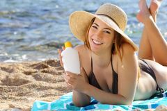Happy woman on the beach showing a sunscreen bottle Stock Images