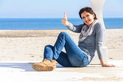 Happy woman on beach thumb up Stock Photos