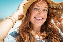 Happy woman on beach wearing straw hat royalty free stock image