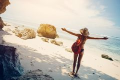 Happy woman on the beach wearing swimming suit, hat and backpack stock photo
