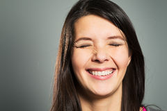 Happy woman with a beaming smile. Happy pleased woman with a beaming toothy smile with her eyes closed, close up facial portrait on a grey studio background Royalty Free Stock Photo