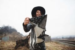 Happy woman in a beautiful gray cardigan and black hat have fun in the countryside stock photo