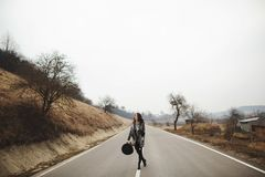 Happy woman in a beautiful gray cardigan and black hat rides along the way royalty free stock photos