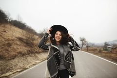 Happy woman in a beautiful gray cardigan and black hat rides along the way royalty free stock images