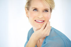 Happy Woman. Beautiful smiling elegant woman indoors wearing blue blouse and short blond hair Stock Photography