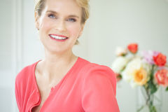 Happy Woman. Beautiful smiling elegant woman indoors wearing pink blouse and short blond hair Royalty Free Stock Photo