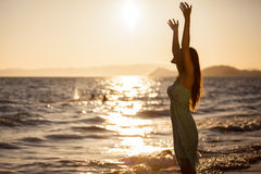 Happy woman and a beautiful sunset Stock Photos