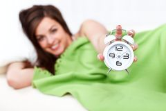 Happy woman in bed with alarm clock Stock Images