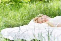 Happy woman on bed on natural background Royalty Free Stock Image