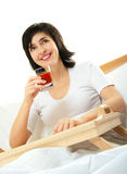 Happy woman in bed with tomato Stock Photography
