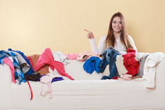 Happy woman behind sofa in messy room at home. Stock Photo