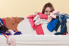 Happy woman behind sofa in messy room at home. Royalty Free Stock Image