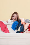 Happy woman behind sofa in messy room at home. Royalty Free Stock Photos