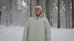 Happy woman in beige coat and pink cap standing in the forest, looking up and smiling. Aged female retiree having rest stock video