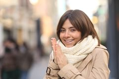 Happy woman being cold in the street in winter stock images