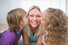 Happy woman being kissed by children Stock Photo