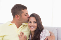 Happy woman being kissed by man Stock Photos