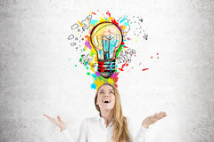 Happy woman with the best idea. Close up of a happy blond businesswoman standing with an open mouth near a concrete wall with a colorful light bulb above her Royalty Free Stock Images