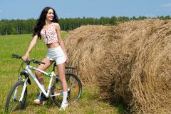 Happy woman on bicycle in the field Royalty Free Stock Images