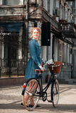 Happy woman with bicycle standing on the street royalty free stock photo