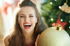 Happy woman with big gold Christmas ball near Christmas tree royalty free stock photography