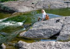 A happy woman on big stone beside rapid stream. Stock Photo
