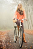 Happy woman with bike bicycle in autumn park. Royalty Free Stock Image