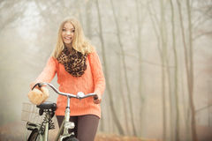 Happy woman with bike bicycle in autumn park. Stock Photo