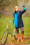 Happy woman with bike in park taking selfie photo. Stock Photo