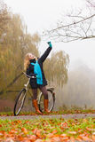 Happy woman with bike in park taking selfie photo. Royalty Free Stock Photos