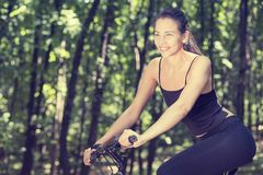 Happy woman on bike standing on a hill road enjoying beautiful summer sunny day Royalty Free Stock Photo