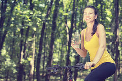 Happy woman on bike standing on a hill road enjoying beautiful v Royalty Free Stock Image