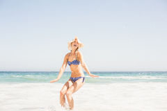 Happy woman in bikini and hat having fun on the beach Royalty Free Stock Photos