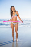Happy woman in bikini playing with hula hoop Stock Photos