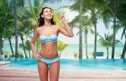 Happy woman in bikini pointing finger up on beach Stock Photos