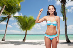 Happy woman in bikini pointing finger up on beach. People, travel, swimwear and summer concept - happy young woman in bikini swimsuit pointing finger up to Stock Images