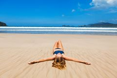 Happy woman in bikini relax, enjoy sunbathing on sand beach. Happy woman in bikini relax and enjoy sunbathing on beach with sea surf. Lying on sand, spread hands Stock Photos