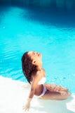 Happy woman in bikini sitting by pool side Stock Photo