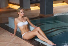 Happy woman in bikini sitting at swimming pool Royalty Free Stock Image