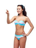 Happy woman in bikini swimsuit pointing finger Stock Photo