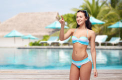 Happy woman in bikini swimsuit pointing finger Stock Photography