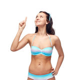 Happy woman in bikini swimsuit pointing finger up Stock Photo