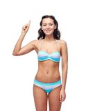 Happy woman in bikini swimsuit pointing finger up Stock Image