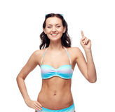 Happy woman in bikini swimsuit pointing finger up Stock Photos