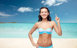Happy woman in bikini swimsuit pointing finger up Royalty Free Stock Image