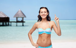 Happy woman in bikini swimsuit pointing finger up Royalty Free Stock Photo