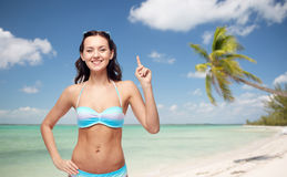 Happy woman in bikini swimsuit pointing finger up. People, travel, tourism, swimwear and summer holidays concept - happy young woman in bikini swimsuit pointing Royalty Free Stock Images